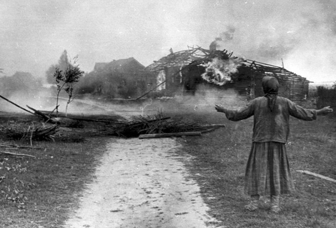 Russian woman watches building burn sometime in 1942 scorched earth